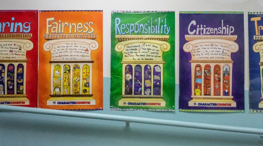 Vibrant character reminder posters hang on the middle school hallway of the City of Knowledge campus, portraying the Six Pillars of Character, which represent core ethical values based on culture. / photo by Ariel Torres