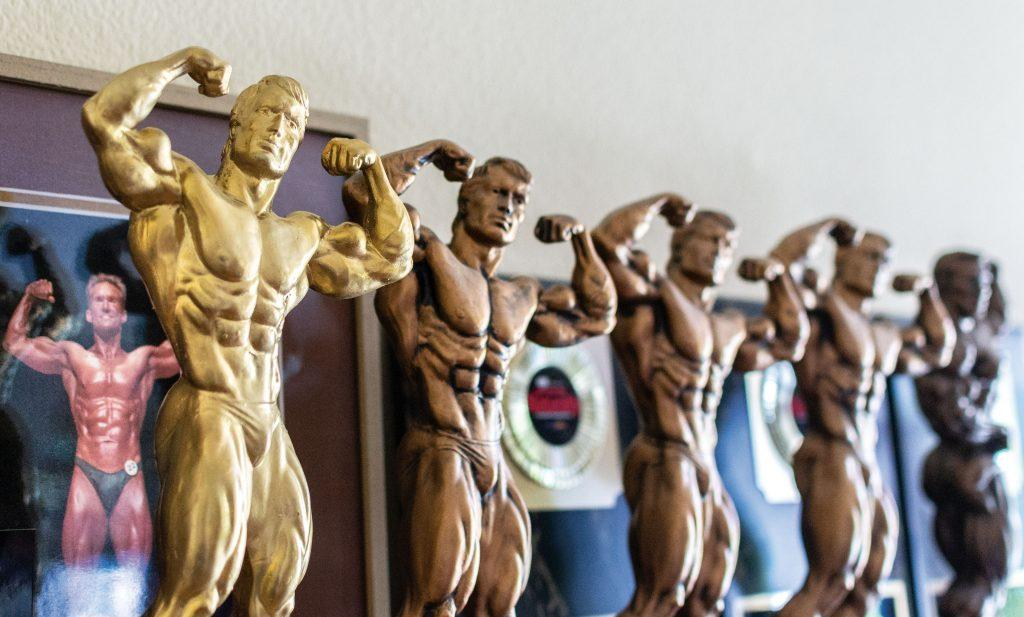 Trophies line the fireplace mantel of Loren Dyck's home in Rialto, along with a picture of Loren competing in the 2005 NPC Tri-State bodybuilding championships. He won the trophies at the GNC IFBB North American Championships over the last two decades. / photo by Molly Garry