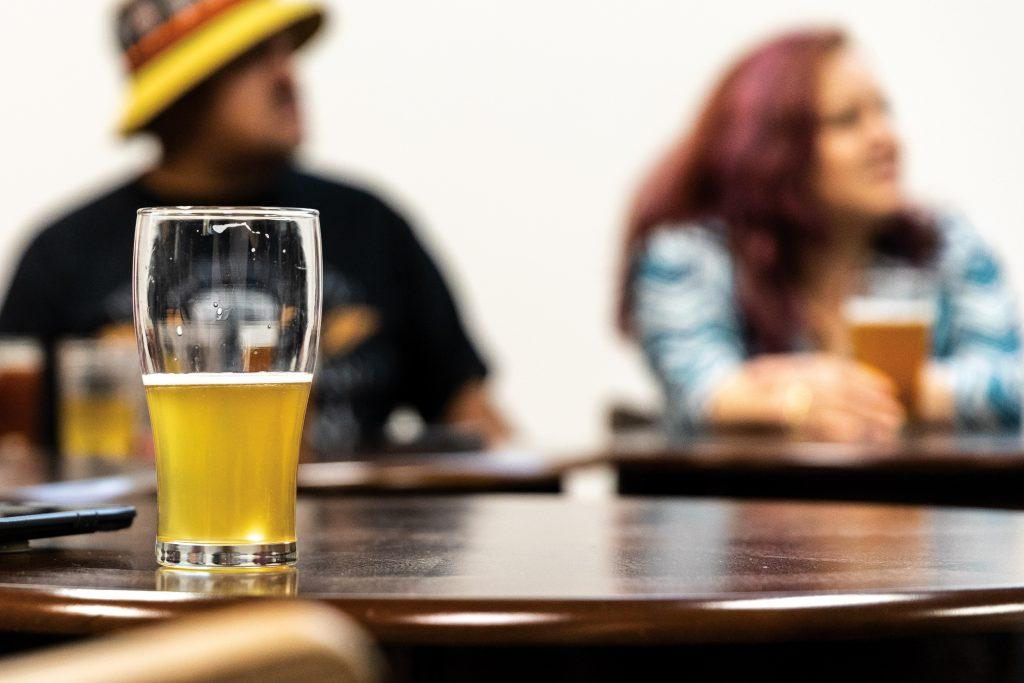 A glass of light beer is left behind by one of the Brew Witches as they socialize through the night. The Brew Witches welcome all genders to attend their events. / photo by Jaren Cyrus