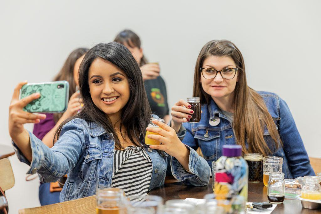Brianna Garcia and Dana Reed take selfies with samples from their beer flight. A flight of beers come with six samples from light to dark. / photo by Jaren Cyrus