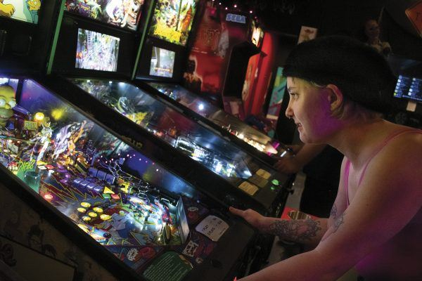 Elizabeth Toeller, one of The Paradox Arcade and Bar's regulars, tries her hand at the Simpson's Pinball Party, which is one of the five pinball machines available at the Pomona arcade. / photo by Maydeen Merino