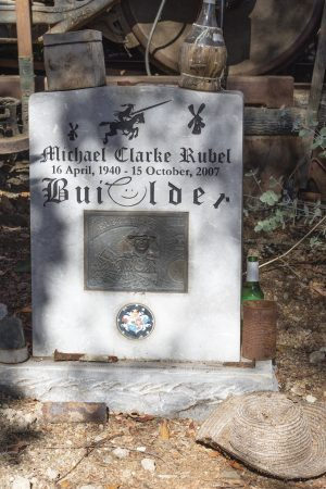 Michael Rubel's memorial headstone sits just behind the red train caboose; a bottle of wine sits atop the faux-grave marker, and an old straw hat of Michael's is placed to the side. / photo by Kayla Salas
