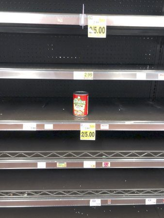 A lone can of pizza sauce is all that's left on the grocery store shelves as shoppers race to stock their pantries. / photo by Emily J. Sullivan