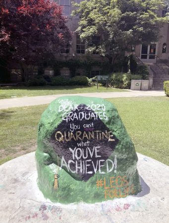 Once a hub for the daily hustle and bustle at the University of La Verne, the freshly painted rock sits lonely in front of a deserted Founders Hall, a beacon of hope and perseverance for graduating students. / photo by Remy Hogan