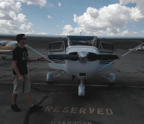 Jared Carey, 18, does a preliminary check of the Cessna 174 he's about to fly. He checks the weight and balance of the plane and makes sure the instruments are working. / photo by Lindsey Gooding