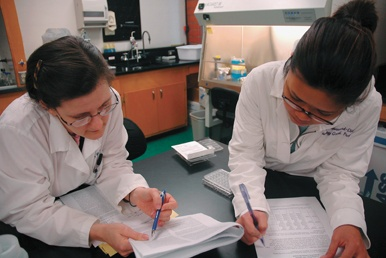 """Christine Broussard takes off her dancing shoes and puts on her white lab coat to fulfill her other passion: testing the effects of the pesticide Methoxychlor on the immune system. """"She's great; She's very helpful,"""" says Joan Ordonez of her senior project adviser. / photo by Reina Santa Cruz"""