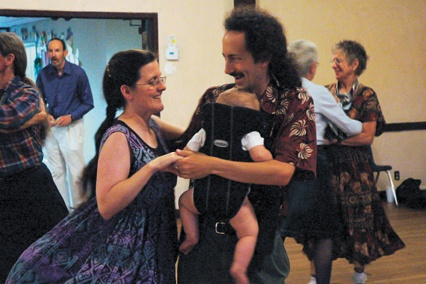 Twirling skirts, wide smiles and deep eye contact tell the story of Contra Dancing. Christine Broussard, ULV biology professor, husband Jeremy Korr and 8-month-old Gabriel join in this family dance. / photo by Reina Santa Cruz