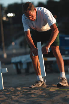 Steve Davis, of Santa Monica, plants a cross on the beach. He's one of the first volunteers there on Sundays to begin the long process of setting up the memorial. / photo by Lindsey Gooding