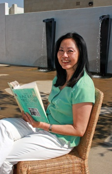 "Sitting at the courtyard of the new Hotel Casa 425 in Claremont, author Duong Van Mai Elliott reads her literary success, ""The Sacred Willow."" Elliott, now a resident of Claremont, lives with her husband and many artifacts they have collected from their world travels. / photo by Catherine Campos"