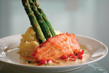 Pan-seared salmon served over tomato and scallion burr blanc sauce, with blanched asparagus and whipped Yukon Gold potatoes. Total preparation time: 45 minutes. / photo by Reina Santa Cruz