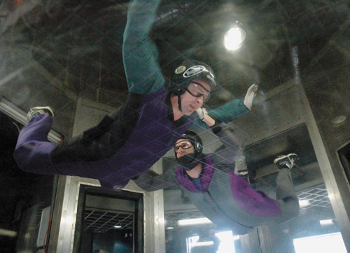 Flight instructors Scott Levesque and Steven Straley train together in the wind tunnel. Both instructors take turns pretending to be flight students who need help. The instructors go through worst-case scenario training. / photo by Reina Santa Cruz