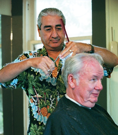 In his downtown red Bonita Avenue house is where La Verne hair stylist Abel Gandara can be found between clients like Orval Kidwell (above). Abel, a barber for 36 years, graduated from San Bernardino's American Barber College. A 1966 Bonita High School graduate, he received a $100 Bonita scholarship toward his trade school education. / photo by Liz Lucsko