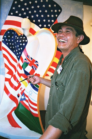 "Painting the finishing touches on the Fairplex's archangel in the Millard Sheets Gallery on the last day of the Los Angeles County Fair, Sept. 29, 2002, Alex Zegouvia answers questions poised to him as he paints the words ""unity"" and ""diversity"" on the outer edge of the life-sized sculpture's wings. / photo by Liz Lucsko"