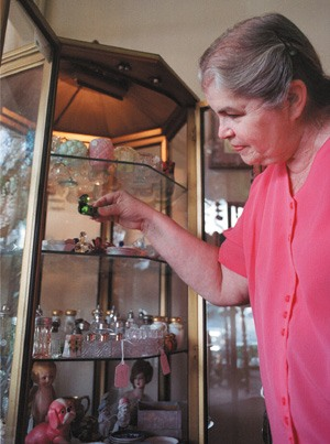 """In her free time, Betty Klousek dusts, cleans and arranges the way her antique displays look. When holidays approach, Klousek tries to arrange the store's design to correspond with the theme of the holiday. Klousek and her daughter Rebecca, who co-owns Generations, share duties that include polishing silver, restoring old furniture and replacing missing beads and gems. """"The things are made so much better than anything we have nowadays. And everything was made by hand with care. Things made of natural wood, it's not glued together sawdust,"""" Klousek says. / photo by Matt Wright"""