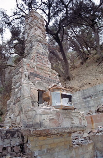 One resident's labor of love still shows in the intricate fireplace rock work a quarter of a mile up the west fork. At least one resident sleeps under a tarp on the charred foundation of his home. / photo by Amy Babin