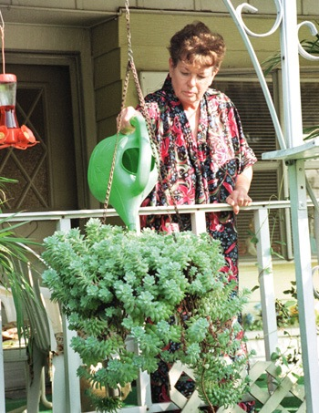 With a green thumb and a green watering can, Lorraine Berten, a 13-year resident of Twin Oaks Mobile Home Park in eastern La Verne, tends to her plants. She also loves to sit on her porch and listen to her wind chimes while whistling at her two cockatiels. / photo by Echelle Avelar