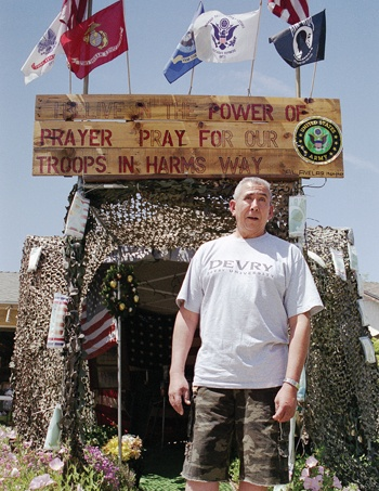 Displaying his public prayer plea, Alfredo Avelar, a La Verne Vietnam veteran, shows his appreciation for the soldiers in Iraq with mementos of American pride. His proudly created military bivouac resides in his Damien Avenue front yard and is open to the public. / photo by Emmah Obradovich