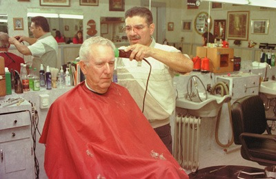Dan Perea, stylist, and David Voors, client, are key players in the small town ritual at Fred's Barber Shop in La Verne. While the haircut may be the up-front reason for going to the shop, the conversation is the key element that brings customers back. / photo by Alen Zilic