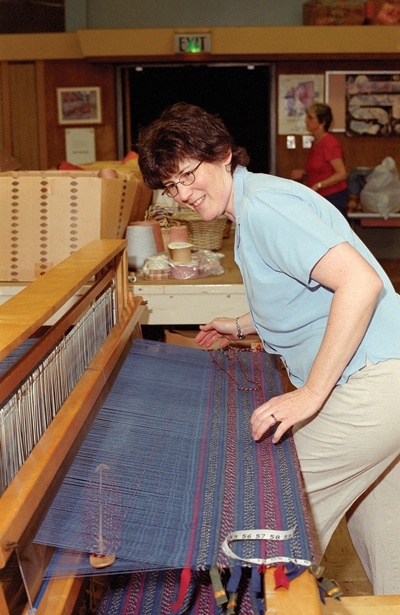 As if hanging 10 on the most complicated surfboard in the world, Kathleen Waln, 41, inches closer to finishing her creation for her Victorian home, a rug using a shaker pattern. Waln employs a single weave, interlaced with an intricate weft, which is made of the horizontal threads interlaced through the woven fabric. / photo by Gloria Diaz