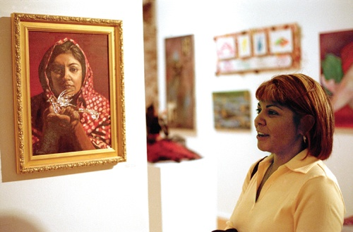 "Like looking at herself in a past life, Concepcion Rodriguez explains how she painted her self-portrait,""La Ofrenda,"" translated, ""the offering,"" by looking at a photograph her husband took of her. Rodriguez's painting was part of the ""Simply Red"" art show at the dA Center for the Arts Gallery in Pomona. / photo by Blanca Rocha"