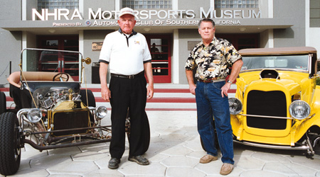 "Drag racing history makers Keril Keiser, Pomona native, (left) winner of the first drag racing trophy in the Inland Valley, and Dean Lowell, La Verne, who raced in the first Pomona Winternationals in 1961 remember fondly their glory days. Lowell stands by a car that is an exact replica of the one he raced in that first race, while Keiser stands near a classic style Ford. Says Keiser, ""Back then, you couldn't afford to put a good paint job on a car-all the money went under the hood. Painted fire flames on the side? That's not how the real racers looked."" / photo by Liz Lucsko"