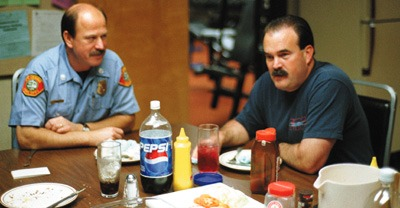 Relaxing in the moments before the picnic setting is interrupted by the emergency alarm, Captain John Chappell (left) and fireman Keith Thompson follow up grilled hamburgers with a recollection of station pranks. / photo by Matt Wright