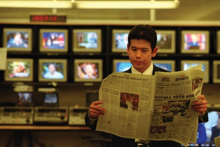 """After receiving word that his 5 p.m. sports segment will be cancelled by breaking news in the Elizabeth Smart case, KABC sports anchor Rob Fukuzaki scans the sports section for """"Fuk's Follies"""" bloopers. The 1988 University of La Verne Communications Department alumnus has become a news celebrity face on Channel 7's Eyewitness News. / photo by Liz Lucsko"""
