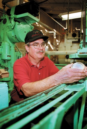 "Once the fastest canning machine in the industry, the ""Panama Paddle Packer,"" named after the Panama Canal, is still used today by Cliff Graber and his Graber Olive Company. / photo by Tom Galaraga"