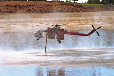 Looking like a giant firefly, Sikorsky S-64 Skycranes were used to fight the Williams wildfire. La Verne's Live Oak Reservoir supplied the water for the helicopters. / photo by Liz Lucsko