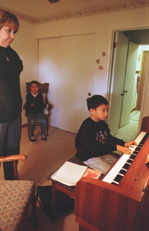 "Mary Beth Warfel, a La Verne piano teacher, steadily eyes the hands of Carlyle Rubin, 8, as Brian Brophy, 10, patiently waits his turn. Warfel, like many business people, has turned to the comforts of home as her workplace. ""I'm booked for two years,"" says Warfel, whose students range from young children to adults. / photo by Christie Reed"