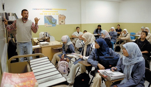 At the bell, Jason Schmidt rushes a few final words as his 8th and 9th grade English students hover an inch above their chairs. At the WASC accredited school, boys dress conservatively, and girls begin wearing the hijab around age 9. / photo by Adam Omernik