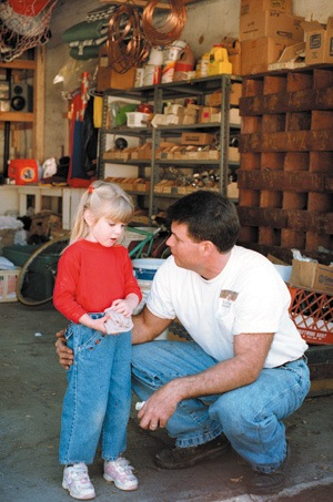 Tim Loughman takes a few minutes from work to chat with his daughter, Shelby Anna Loughman. Although being self-employed forces Tim Loughman to work longer hours than most, he always finds time to spend with his family at home. / photo by Juan Garcia