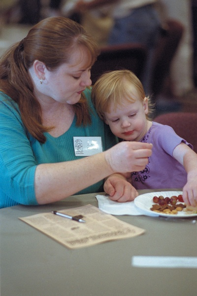 Sinda Calvert and daughter Paige snack before the monthly meeting for the Moms Club. / photo by Sylvia Castellanos