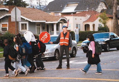 Orville Powell, 78, has been stopping traffic on the corner of D and Sixth streets in order to help school children get across the street safely for more than a decade. He became a crossing guard a few years after his retirement from a Pomona welding shop in 1987. / photo by Juan Garcia