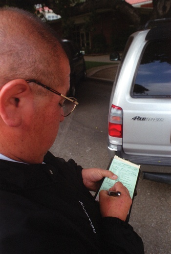 """Sometimes I'll go through a whole book in a day,"" says Henry Negrette. With people parking everywhere, short of the sidewalk, Negrette, one of five of ULV's campus safety officers, has plenty of reasons to put his pen to work. A parking ticket can set violators back $20 to $330. / photo by Jason Cooper"