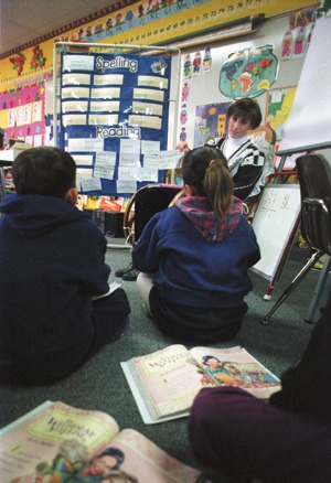 From a child's perspective, the effects of class-size reduction are insignificant. But to Lisa Young, a second-third grade combination teacher at Oak Mesa Elementary School, the 20:1 student-teacher ratio has mandated that she balance the workload of two curriculums. / photo by Michael P. Bailey