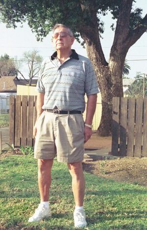 """With his feet firmly planted in La Verne, Robert Rodriguez, city councilman and father of four successful children, stands near the 68-year-old oak tree planted on the day he was born. Rodriguez, recently retired as head of security for the University of La Verne, spends his free time in his own garden, serving as """"housewife,"""" while his wife Fran spends her days punching numbers as student accounts director at ULV. / photo by Summer Herndon"""