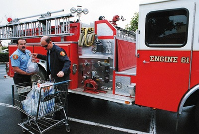 """Over here, Over here!"" calls out a little boy, waving to firefighters shopping at Albertsons. Thompson and Chappell realize that they are on public display, 48 hours, from extinguishing fires to waving to children at the supermarket. / photo by Matt Wright"