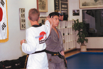 Master Jin Bae of the Sunrise Tae Kwon Do studio of La Verne instructs students through a student-teacher demonstration of the next technique the class is to learn. Bae offers classes for everyone from beginners to black belts with students ranging from small children through adults. / photo by Erica Paal