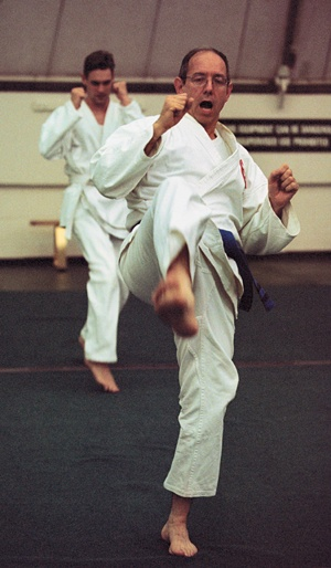 In a symbolic act of defense, Brian Tresner, network/computer lab support manager at ULV, takes part in his ULV Tae Kwon Do class with Adam Porpora (rear). Tresner holds a blue belt in the sport he has practiced for five years with wife Penny, holder of a first red belt. Toks Oduwole instructs the ULV activity class. / photo by Liz Lucsko
