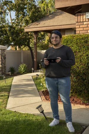 """While escaping from the realities of virtual classes, David Gonzalez, senior journalism major, becomes another version of himself while playing """"Animal Crossing: New Horizons"""" for the Nintendo Switch. / photo by Maxwell Sierra"""