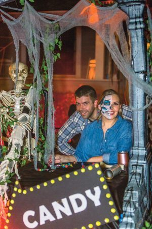 David and Mallory Olsen in La Verne embrace the Halloween spirit despite COVID-19 raging through Los Angeles County. Their spectacularly decorated front lawn booth readily caught the attention of masked trick-or-treaters walking by on Halloween night. / photo by Mya-Lin Lewis