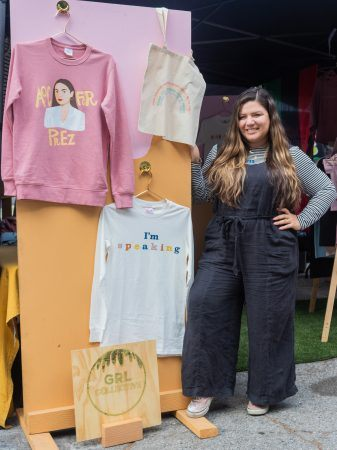 """Kristine Rodriguez, University of La Verne Alumna and Founder of GRL Collective, wears her GRL Collective x Noelle Gomez Fringe Mask as she displays """"AOC for Prez"""" sweater and """"I'm Speaking"""" shirt inspired by Vice President Elect Kamala Harris at the Melrose Trading Post flea market. GRL Collective products are listed on the website grlcollective.com. / photo by Christine Diaz"""
