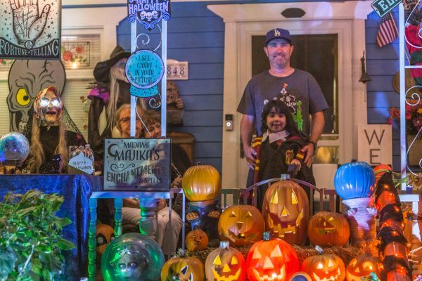 Dressed as a young Hogwarts student, Rose Murphy and her family stand behind a barricade of pumpkins in front of their spectacularly decorated house, complete with skeletons and various fortune telling elements. / photo by Mya-Lin Lewis